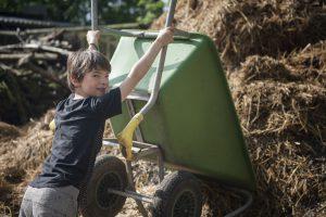 Kind en kruiwagen bij mestvaalt